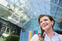 Detail of smiling businesswoman against glassy modern office building. Close up of smiling elegant businesswoman in pink jacket and white shirt against glassy royalty free stock images