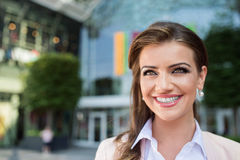 Detail of smiling businesswoman against glassy modern office bui Royalty Free Stock Photography