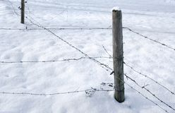 Snowbound barbed wire fence Royalty Free Stock Images