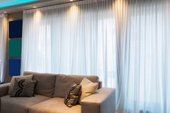 Detail of sofa in modern apartment. With a big window and frames royalty free stock image