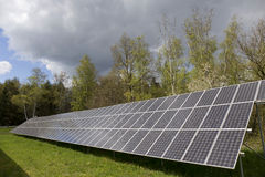 Detail of the Solar Power Station on the spring flowering Meadow in the sunny Day Stock Photo