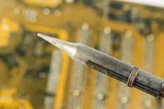 Detail of soldering iron over printed circuit board Stock Photography