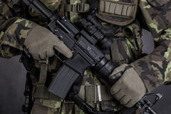 Detail of a soldier holding modern weapon M4. Close-up of a soldier holding modern weapon M4 carbine Royalty Free Stock Photos