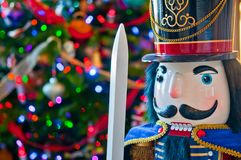 Detail of Soldier Nutcracker with Christmas Tree Bokeh Background. Head of Toy Soldier Nutcracker with Colorfully Lit and Decorated Christmas Tree in Bokeh stock photo