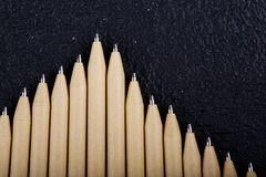 Shallow focus view of a close-up image of new pen pencils seen on dark black background. mock up. Detail of some of the beige pen pencil tips is evident, seen on royalty free stock photos