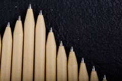 Shallow focus view of a close-up image of new pen pencils seen on dark black background. mock up. Detail of some of the beige pen pencil tips is evident, seen on stock photos