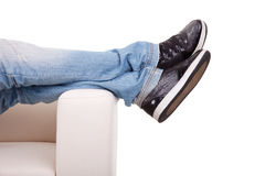 Detail, of some legs stretched on the couch Stock Images