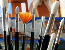 Brushes and canvas in the background. Detail of some types of acrylic paint brushes with an unfinished canvas at the bottom on an easel Royalty Free Stock Image