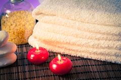 Detail of spa massage border with towel stacked stone and red candles warm atmosphere Royalty Free Stock Photography