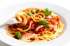 Detail of spaghetti rolled onto fork, tomato sauce, basil and ch Stock Photos