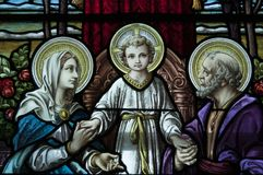 Detail of stained glass window in an old church. Close up photo of a beautiful stained glass window found in an old church depicting Jesus, Mary & Joseph Royalty Free Stock Photos