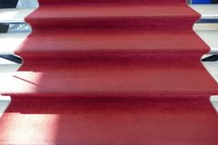 Detail of stairs with a red carpet. A detail of stairs with a red carpet Stock Image