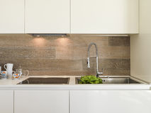 Detail of steel faucet in a modern kitchen. With wooden panels royalty free stock photo