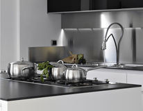 Detail of steel saucepans in a kitchen. With parsley into Stock Photography