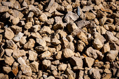 Detail of stone. Detail of a pile of stones used as aggregate in the construction industry, side-lit by strong sun light Royalty Free Stock Photos