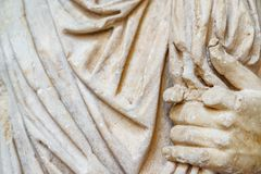 Stone statue with toga and hand. Detail of stone statue with toga and hand Royalty Free Stock Photo