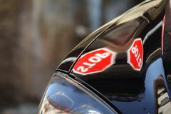 STOP signal over black vehicle hood with shallow depth of field royalty free stock images