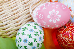 Detail of strawy basket with Easter eggs and velvet Royalty Free Stock Photo