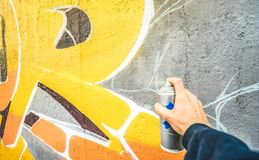 Detail of street artist painting colorful graffiti on public wall stock images