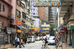 Detail of a street in central Hong Kong with many people walking on the street. On background local shops and restaurants Royalty Free Stock Images