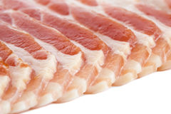 Detail of strips of streaky uncooked bacon. Detail of strips of streaky uncooked bacon isolated on white royalty free stock photos
