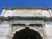 Detail of the superior part of the arc of Costantino in Rome Italy. Travel destination. Blue clear sky. Sunny day. White triumphal arch. Written in Latin Stock Images