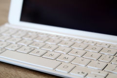 Detail of tablet with modern white keyboard. Photo of detail of tablet with modern white keyboard stock photo