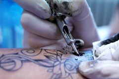 Detail of tattoo making - ink, machine and hands in gloves Stock Images