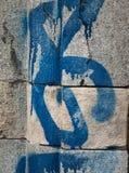 Detail of textured grey masonry  blue and white graffiti Royalty Free Stock Photos