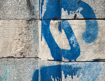 Detail of textured stonework with blue graffiti Royalty Free Stock Images