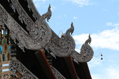 Detail from a Thai Temple Roof. This image shows three decorative finials on a temple roof in Northern Thailand.The background is a blue sky with white clouds Stock Image