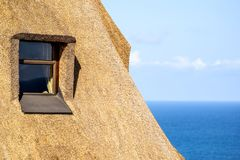 Detail of a thatched roof house using reed grass as building material. Windows visible and the ocean in the background. Thatched roof cottages are following a stock images