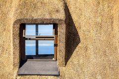 Detail of a thatched roof house using reed grass as building material. Windows visible and the ocean in the background. Thatched roof cottages are following a stock photos