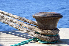 Detail of thick boat ropes tied to an old rusty bollard Stock Photo