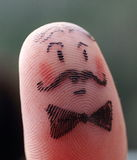 Detail of thumb finger painted with a funny man face Royalty Free Stock Photography
