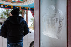 Detail of Tibetan glass decoration of the hotel with tourist on the left in Lachung in winter. North Sikkim, India Royalty Free Stock Image