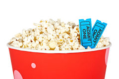 Detail of tickets and popcorn. Detail of popcorn in a bucket and two tickets over a white background. Tickets on focus and shallow depth of field Stock Images