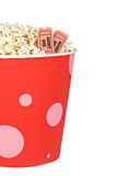 Detail of tickets and popcorn. Detail of popcorn in a bucket and two tickets over a white background. Tickets on focus and shallow depth of field Stock Photo