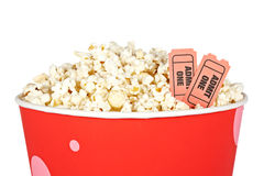 Detail of tickets and popcorn. Detail of popcorn in a bucket and two tickets over a white background. Tickets on focus and shallow depth of field Stock Image