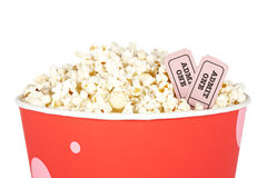 Detail of tickets and popcorn. Detail of popcorn in a bucket and two tickets over a white background. Tickets on focus and shallow depth of field Stock Photos