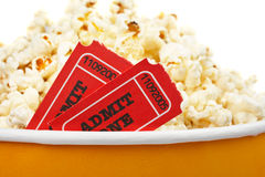 Detail of tickets and popcorn. Detail of popcorn in a bucket and two tickets over a white background. Tickets on focus and shallow DOF Stock Photography