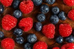 Detail top view on mixed blueberries and raspberries on wooden p. Late Stock Image