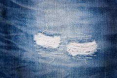 Detail of torn blue denim. Front view royalty free stock images