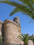 Detail of a tower of the fortress of San Gallo, medieval castle of Neptune Italy. Blue clear sky. Sunny day. Travel destination. Green palms. Bricks round Royalty Free Stock Image