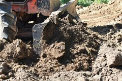 Tractor push clot soil after pour from truck. Detail tractor push clot soil after pour from truck Royalty Free Stock Image