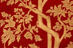 Traditional red painting depicting trees and leaves on a door at the the Wat Phra Kaew Palace, also known as the Emerald Buddha Te. Detail of traditional red Stock Photos