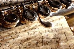Detail transverse flute on old handwritten sheet music Stock Image