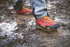 Detail of trekking boots in a mud. Muddy hiking boots and splash of water. Man splashing in muddy and water in the countryside. Detail of trekking boots in a stock image