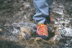 Detail of trekking boots in a mud. Muddy hiking boots and splash of water. Man splashing in muddy and water in the countryside. Detail of trekking boots in a stock photo