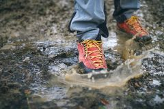 Detail of trekking boots in a mud. Muddy hiking boots and splash of water. Man splashing in muddy and water in the countryside. Detail of trekking boots in a royalty free stock photo